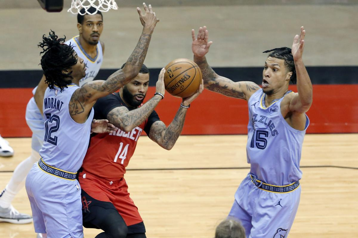 DJ Augustin drives into three Memphis defenders. AP Photo