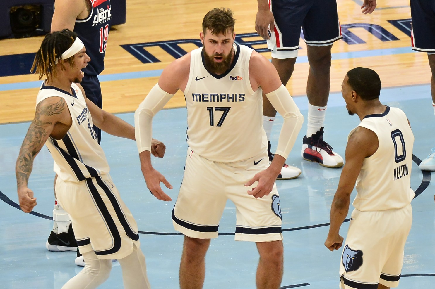 Memphis Grizzlies center Jonas Valanciunas (17) reacts with teammates Brandon Clarke (15) and De'Anthony Melton (0) after scoring in the second half of an NBA basketball game against the Washington Wizards Wednesday, March 10, 2021, in Memphis, Tenn. (AP Photo/Brandon Dill)